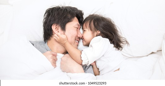 Father and daughter laughing and bonding in bed. Daddy and his little girl spending bed time at home. Single dad fun love family lifestyle father's day concept banner