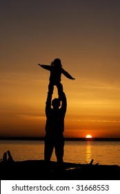 Father with daughter laughing at sunset