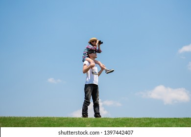 Father and daughter looking afar with binoculars
