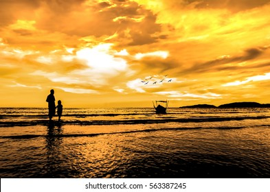 Father and daughter looking to the boat at the beach when sun goes down