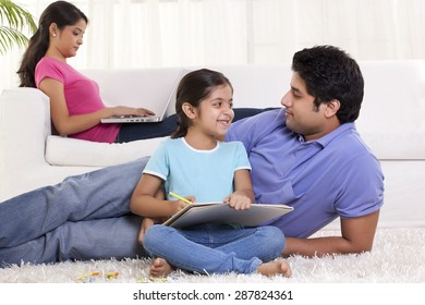 Father and daughter looking at each other while mother using laptop in the background