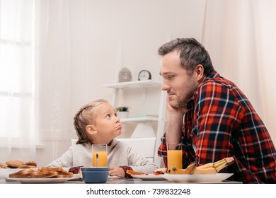 father and daughter looking at each other while having breakfast together