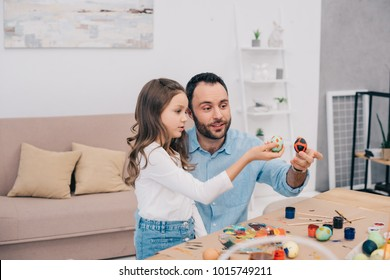 father with daughter looking at freshly painted easter eggs