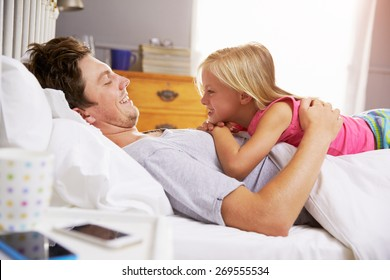 Father And Daughter Lying In Bed Together