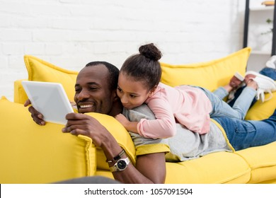 father and daughter lying on couch together and using tablet