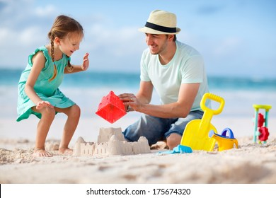 Father and daughter on beach building sand castle