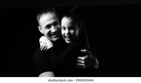 father and daughter on black background