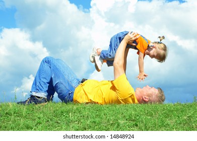 father with daughter on green grass under sky with clouds