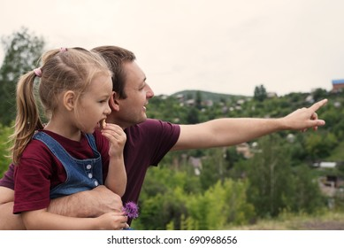 Father and daughter on a hill
