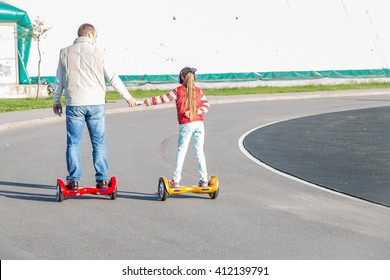 Father and daughter on shoulders riding on modern red and yellow electric mini hover board scooters
