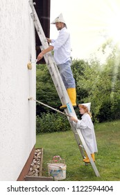 A Father and Daughter painting a house on a ladder