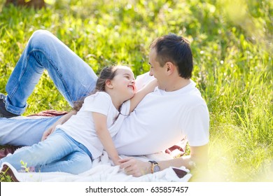 father and daughter in the park Father and daughter laugh lying on the grass