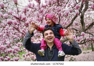 father and daughter play in a garden - spring