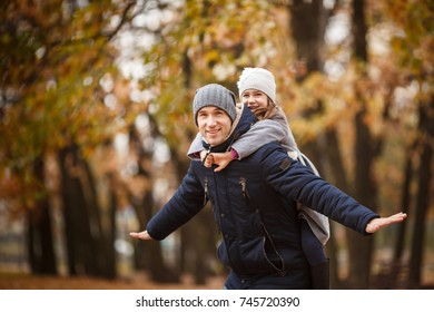 Father and daughter playing in autumn park. Concept of friendly family.