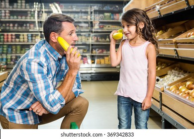 Father and daughter playing with bananas in grocery store