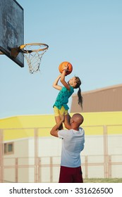 father and daughter playing basketball in the street