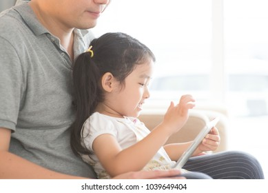 Father and daughter playing with digital tablet on sofa. Asian family at home, living lifestyle indoors.