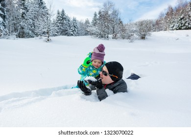 Father and daughter playing in fresh snow.