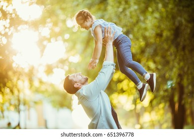 Father and daughter are playing and hugging outdoors in summer park on sunset.