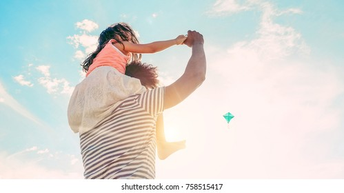 Father with daughter playing with kite and having fun on the beach - Dad enjoying time with his kid outdoor - Family relationship and love concept - Focus child body - Sunset colors tones filter