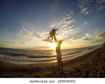 Father and daughter playing on the beach at the sunset time. People having fun. Concept of friendly family and of summer vacation.