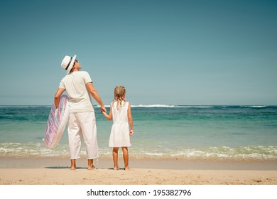father and daughter playing on the beach at the day time