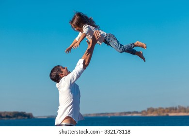 father and daughter playing on the beach at the day time.  fly.