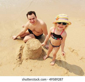 father and daughter playing on the beach with sand