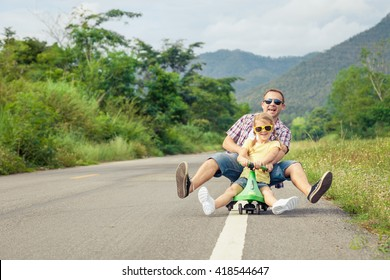 Father and daughter playing  on the road at the day time.  Concept of friendly family.