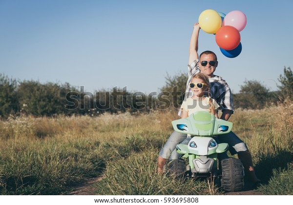 Father and daughter playing on the road at the day time. They driving on quad bike in the park. People having fun on the nature. Concept of friendly family.