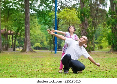 Father and daughter playing at outdoor garden park. Happy Southeast Asian family living lifestyle.
