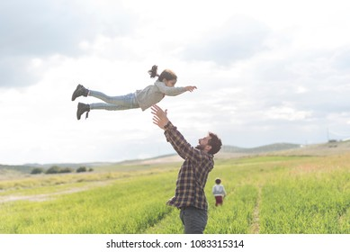 Father and daughter playing outdoors, girl flying on air