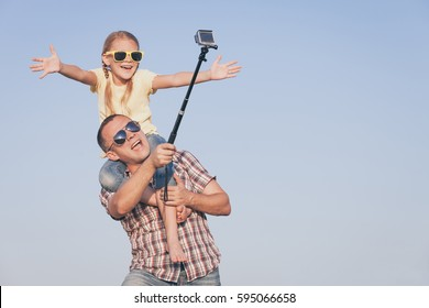 Father and daughter playing in the park  at the day time. Concept of friendly family. Picture made on the background of blue sky.