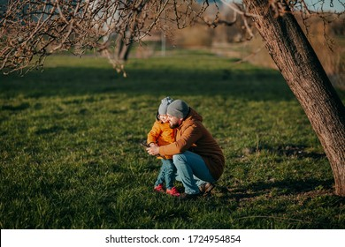 Father and daughter playing in park on green grass. Father's day. Little girl plays with dad outside. Father hugging daughter.