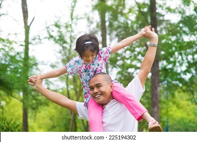 Father and daughter playing piggy back at outdoor garden park. Happy Southeast Asian family living lifestyle.
