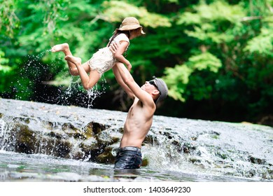 Father and daughter playing in the river