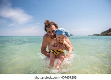Father with daughter playing in the sea.Summer vacations with child.