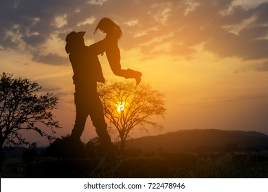 Father and daughter playing at the sunset time. Concept of happy friendly family. High on a hill in the evening soltse. The concept of oneness with nature, family relationships and values. Camping.