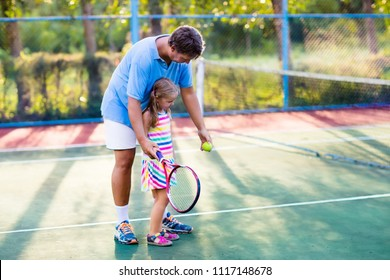 Father and daughter playing tennis on outdoor court. Family with tennis racket and ball at net in sport club. Coach teaching young kid. Child learning to play. Training for kids. Children exercise.