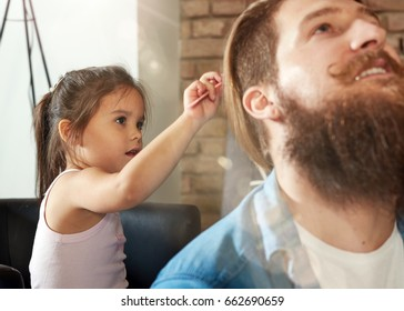 Father and daughter playing together at home, little girl combing father.