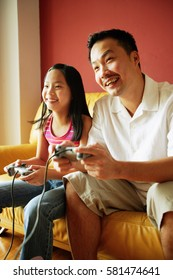 Father and daughter playing video games
