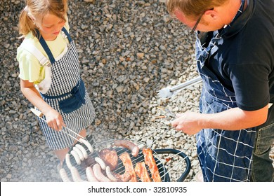 Father and daughter preparing meat and sausages using a barbecue grill
