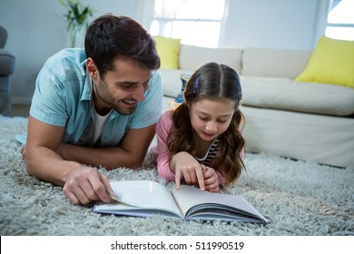 Father and daughter reading book in the living room at home