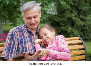Father and daughter reading a book in park