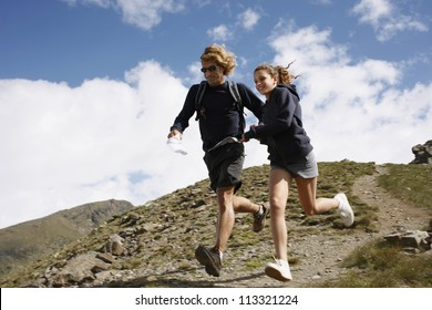Father and daughter running downhill