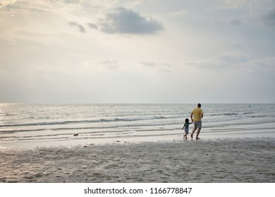 Father and Daughter are running on the beach at Koh Chang, Trat, Thailand in the evening
