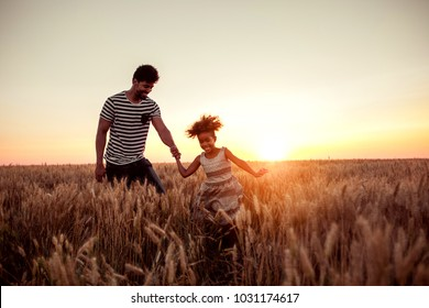 Father and daughter running through the field