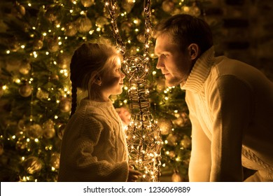 Father and daughter sit near the Christmas tree with decorative deer.