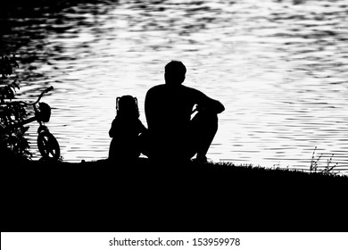 Father and daughter sitting by a lake-Father Day