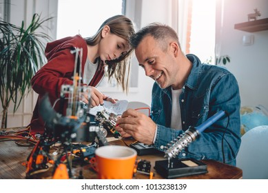 Father and daughter sitting by the wooden table at workshop building robot as a school science project and having fun